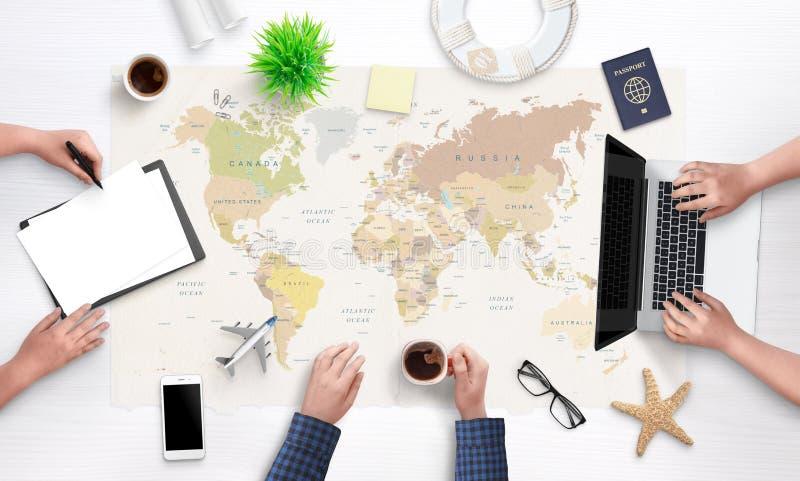 Leute planen eine Feiertagsreise Draufsicht des arbeitenden Schreibtisches der touristischen Agentur mit einer großen Weltkarte i lizenzfreies stockfoto