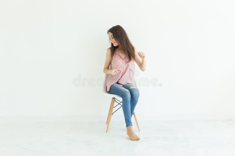 Leute, Schönheit und Modekonzept - junge Brunettefrau, die auf dem Stuhl lokalisiert auf weißem Hintergrund mit Kopienraum aufwir lizenzfreies stockbild