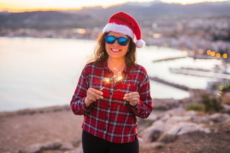 Leute, Schönheit und Weihnachtskonzept - Schönheit in der Sonnenbrille und in der Weihnachtsmann-Hutholding funkelt stockbilder
