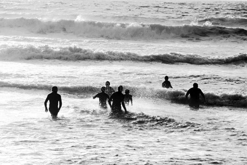 Leute/Schwimmer, die in das Meer laufen stockfoto