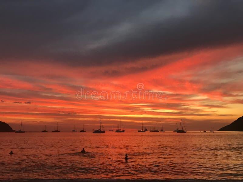 Leute sind Schwimmen im Meer mit dem ?berraschen des roten Brandsonnenuntergangs lizenzfreie stockbilder