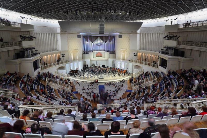 Leute sind Sitze in der Halle vor Konzert lizenzfreie stockfotografie