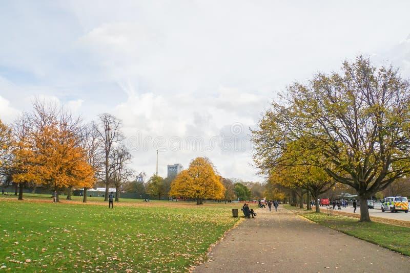 Leute sitzen auf Holzbank und gehen in Hyde Park London stockbild