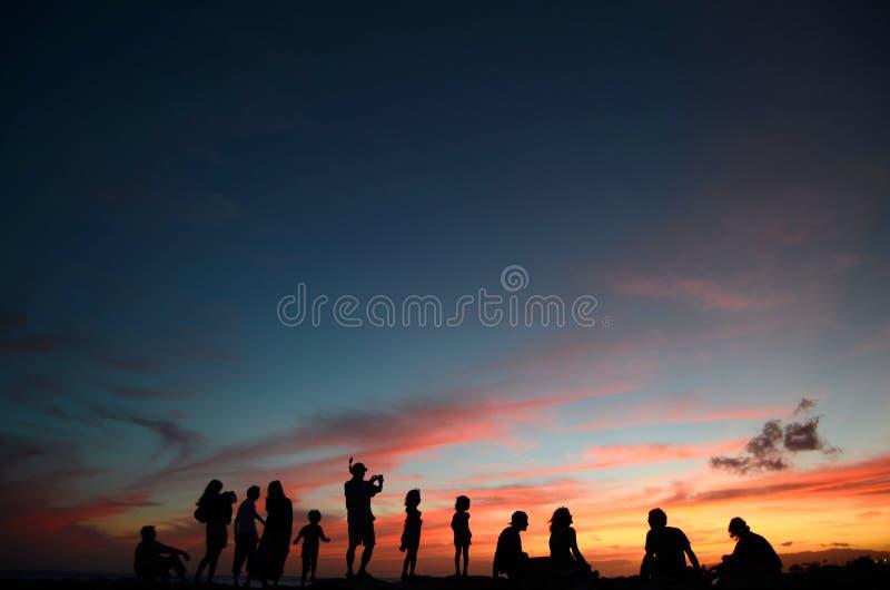 Leute am Sonnenuntergang durch den Strand stockfotografie