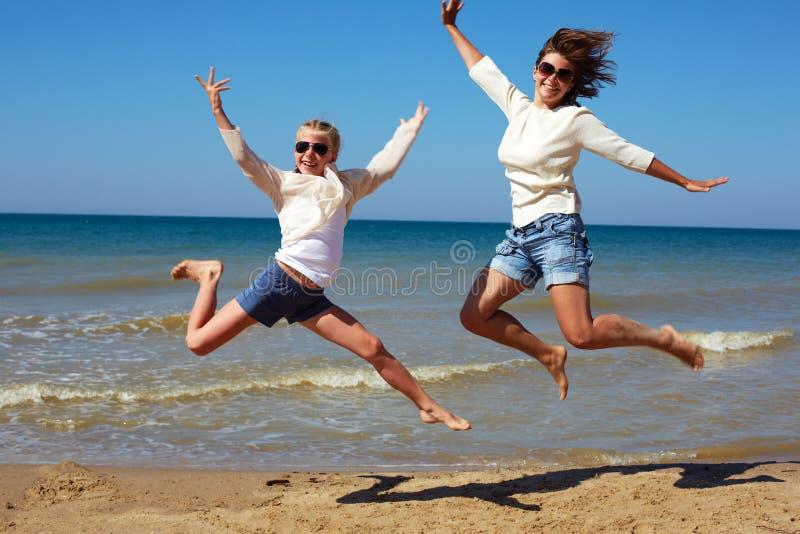 Leute springen vor dem hintergrund des Meeres stockfotografie