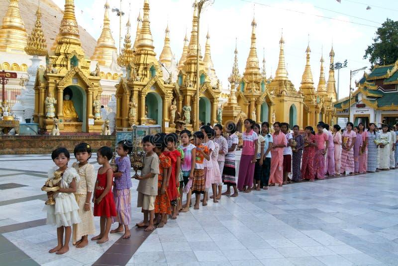 Leute standen mit Angeboten im Bereich der Shwedagon-Pagode herein an stockbild