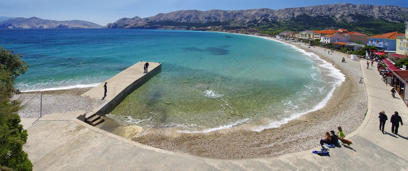 Leute stehen auf Laguna-Strand in der historischen Baska-Stadt auf Krk-Insel am 30. April 2017 still kroatien lizenzfreie stockfotos