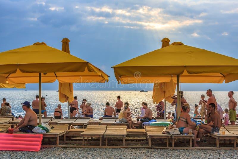 Leute stehen auf steinigem Strand der Schwarzmeerküste unter Zelten bei Sonnenuntergang still lizenzfreie stockfotografie