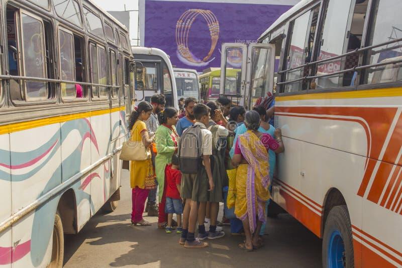 Leute stehen in der Linie am mehrfarbigen Bus am indischen Busbahnhof stockbild