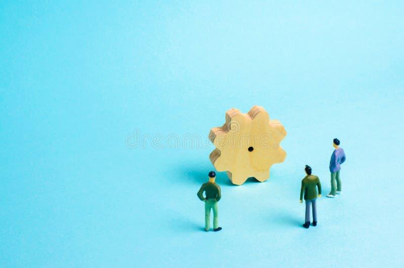 Leute stehen um einen enormen Gang und studieren ihn Konzept von Geschäftsideen, -investitionen und -zusammenarbeit lizenzfreies stockfoto