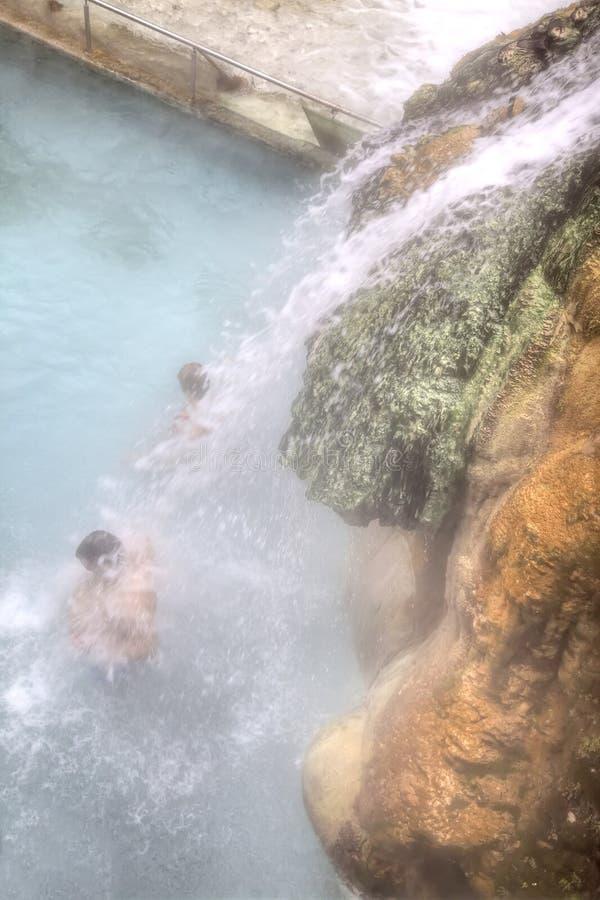 Leute stehen unter den Wasserfalljets mit heilendem Wasser lizenzfreie stockbilder