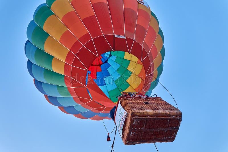 Leute steigen in die Luft im Korb eines enormen mehrfarbigen Ballons stockfoto