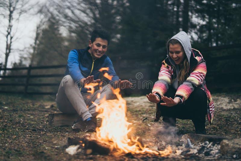 Leute, Tourismus- und Naturkonzept - romantischer Abend, Mann und Frau, die nahe einem Lagerfeuer sitzen stockfoto