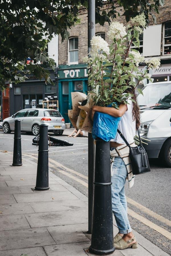 Leute tragen die Anlagen und Blumen, die an der Kolumbien-Straße F gekauft werden lizenzfreie stockfotografie