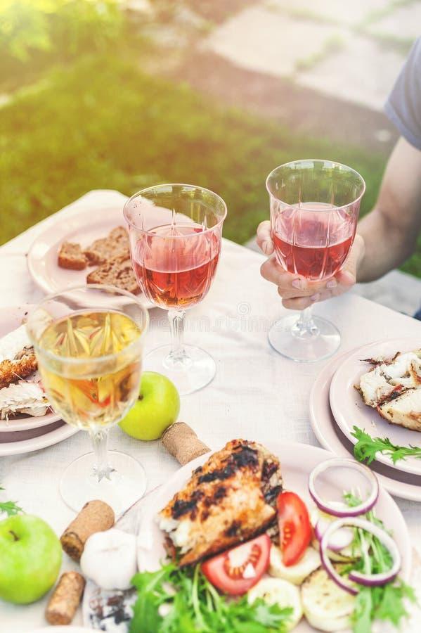 Leute trinken Rose und Weißwein Abendessen mit gegrillten Fischen, Gemüse und Salaten Abendessen im Hinterhof Vertikaler Schuss stockfotos