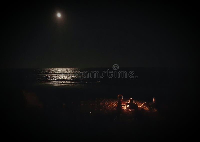 Leute um Lagerfeuer durch Meer stockbilder