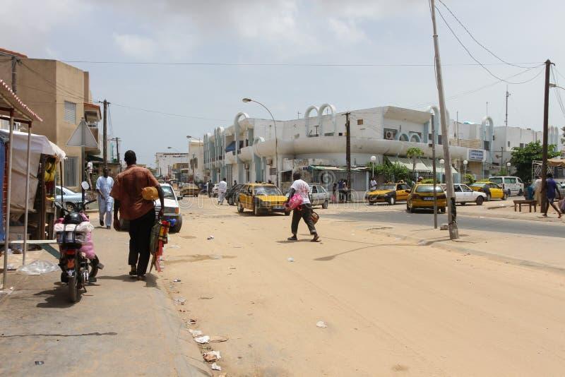 Leute und Autos in einer sandigen Straße in der Stadt von Dakar in Senegal lizenzfreies stockfoto