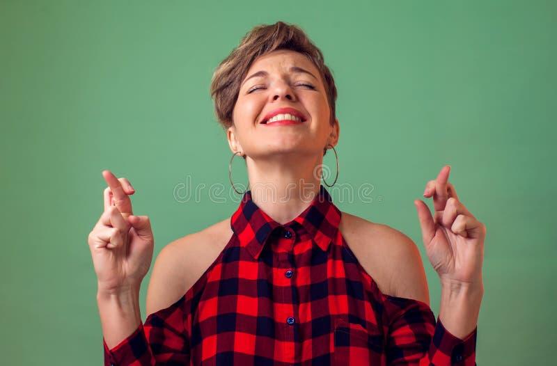 Leute und Gefühle - ein Porträt von lächelnden Frauenkreuzfingern, betet über etwas, Wunschglück, Hoffnungen im Sieg und lizenzfreies stockfoto