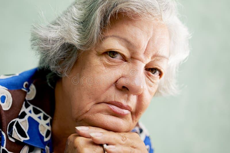 Porträt der ernsten alten Frau, die Kamera mit den Händen auf ch betrachtet stockbilder