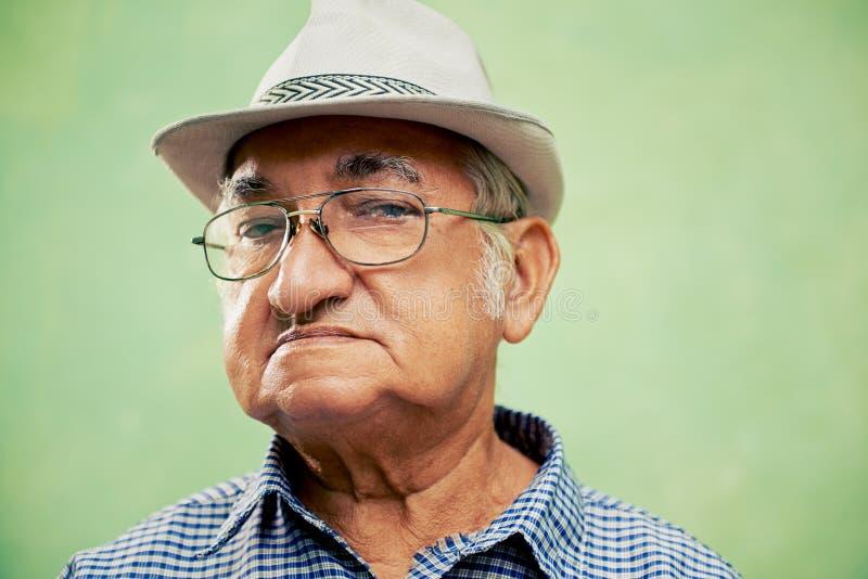 Porträt des ernsten alten Mannes mit dem Hut, der Kamera betrachtet stockfotografie