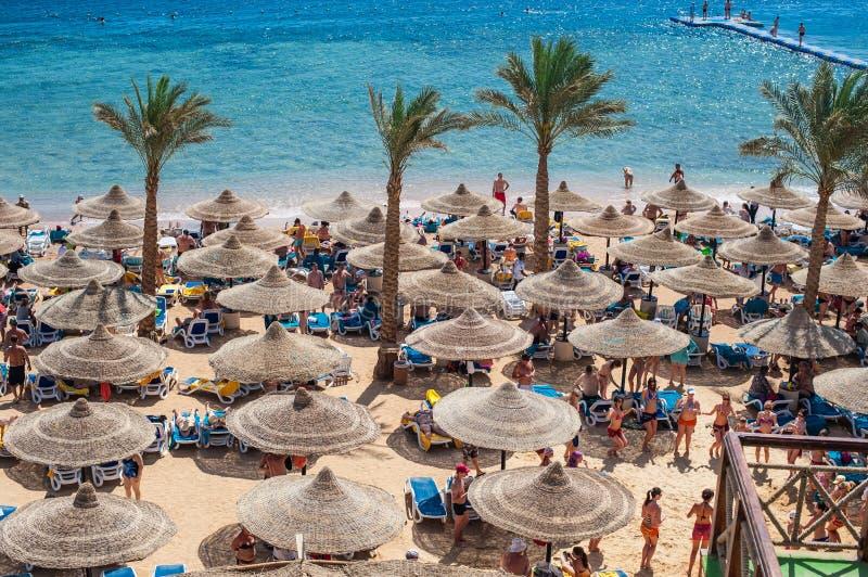 Leute unter Strandschirmen und Seeansicht lizenzfreie stockfotos
