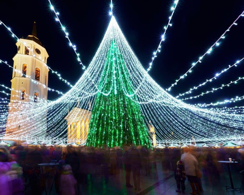 Leute am Vilnius-Weihnachtsmarkt und Weihnachtsbaum nachts lizenzfreies stockbild