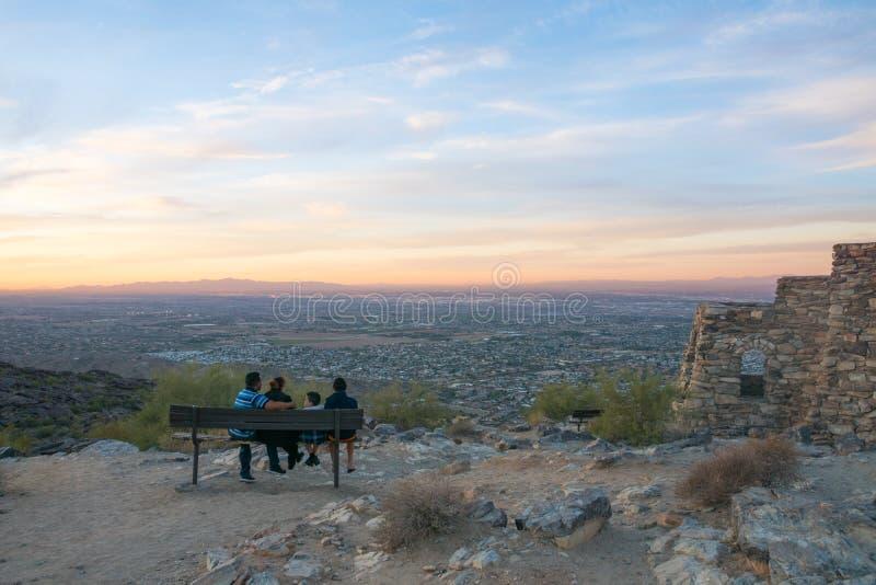 Leute, welche die Ansicht über Stadtzentrum Arizonas Phoenix von den Bergen bei Sonnenuntergang, USA, Panorama genießen stockfotos