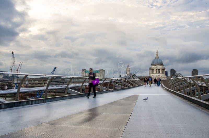 Leute, welche die Jahrtausend-Brücke an einem bewölkten Tag kreuzen lizenzfreie stockfotos
