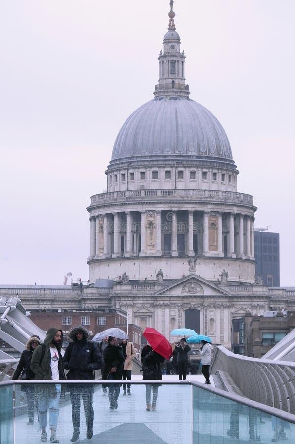 Leute, welche die Jahrtausend-Brücke, London im Regen mit bunten Regenschirmen gegen einen Hintergrund von St- Paul` s Kathedrale lizenzfreies stockbild