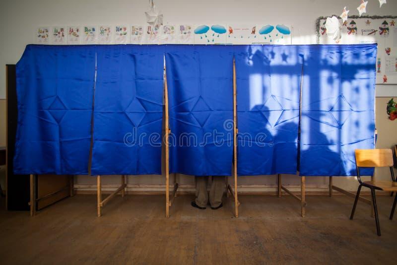 Leuteabstimmung in der Wahlzelle stockbild