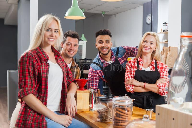Leutefreunde, die das Unterhaltungsc$lachen der Kaffeestube mit dem barista sitzt am Barzähler trinken stockfoto