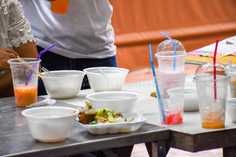 Leutegebrauchsplastik und Schaumbehälter füllen Lebensmittel und trinken es ` s Ursache der Abfall stockbilder