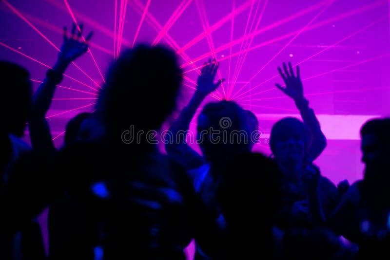 Leutetanzen im Klumpen mit Laser stockfoto