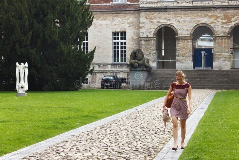 LEUVEN BELGIEN - SEPTEMBER 05, 2014: Okänd ung kvinna på bakgrunden av högskolan för Pauscollege påve` s royaltyfria foton