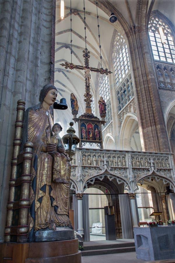Leuven - skepp av St Peters den gotiska domkyrkan och gotisk staty av Madonna royaltyfri fotografi