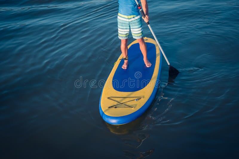 Levántese al hombre de la tarjeta de paleta paddleboarding imagen de archivo libre de regalías