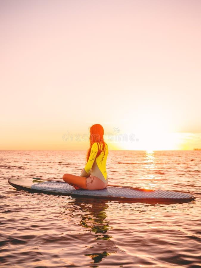Levántese el embarque de la paleta en un mar con colores calientes de la puesta del sol Relajación en el océano imagen de archivo