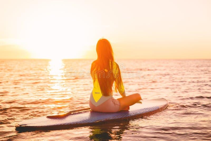 Levántese el embarque de la paleta en un mar reservado con colores de la puesta del sol Meditación de la mujer en tablero del sor imágenes de archivo libres de regalías