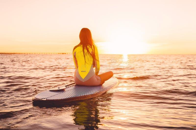 Levántese el embarque de la paleta en un mar reservado con colores de la puesta del sol Relájese en el océano fotografía de archivo