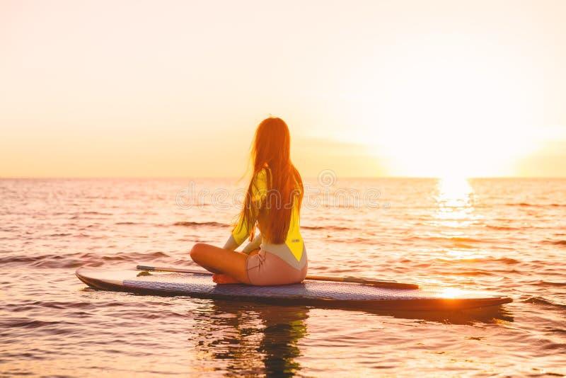 Levántese el embarque de la paleta en un mar reservado con colores de la puesta del sol Relajación en el océano imagen de archivo
