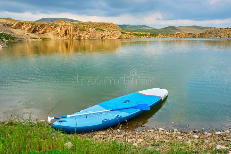 Levántese el SORBO del tablero de paleta en el borde de un smarald/de un lago verde, aislado, aislado, con la luz caliente de la  foto de archivo