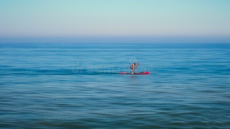 Levántese la colocación paddleboarding del hombre del tablero de paleta en paddleboard foto de archivo libre de regalías
