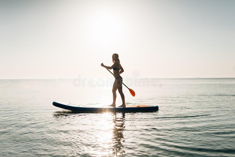 Levántese a la mujer del tablero de paleta paddleboarding en Hawaii que se coloca feliz en paddleboard en el agua azul fotos de archivo