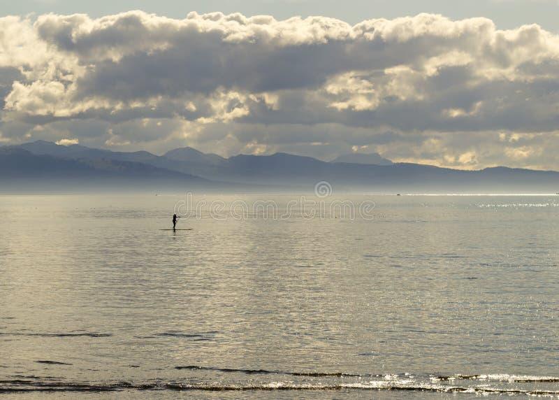 Levántese a la persona que practica surf de la paleta en la oscuridad foto de archivo libre de regalías