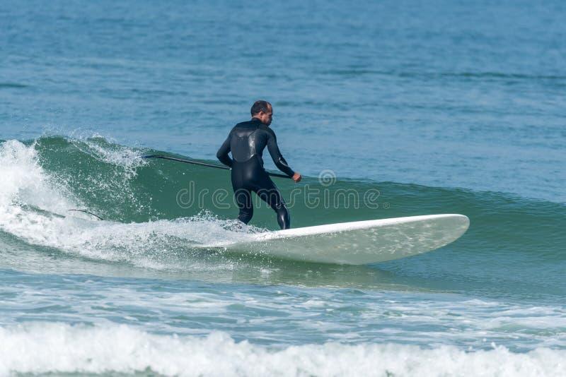 Levántese a la persona que practica surf de la paleta fotografía de archivo libre de regalías