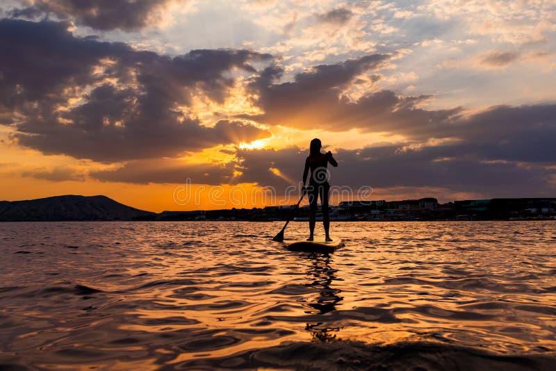 Lev?ntese el embarque de la paleta en un mar reservado con colores calientes de la puesta del sol del verano fotos de archivo