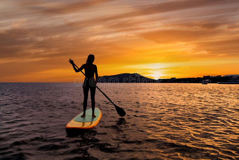 Lev?ntese el embarque de la paleta en un mar reservado con colores calientes de la puesta del sol del verano foto de archivo