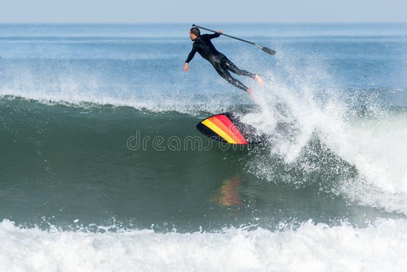 Lev?ntese a la persona que practica surf de la paleta foto de archivo