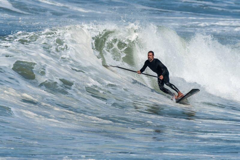 Lev?ntese a la persona que practica surf de la paleta imágenes de archivo libres de regalías