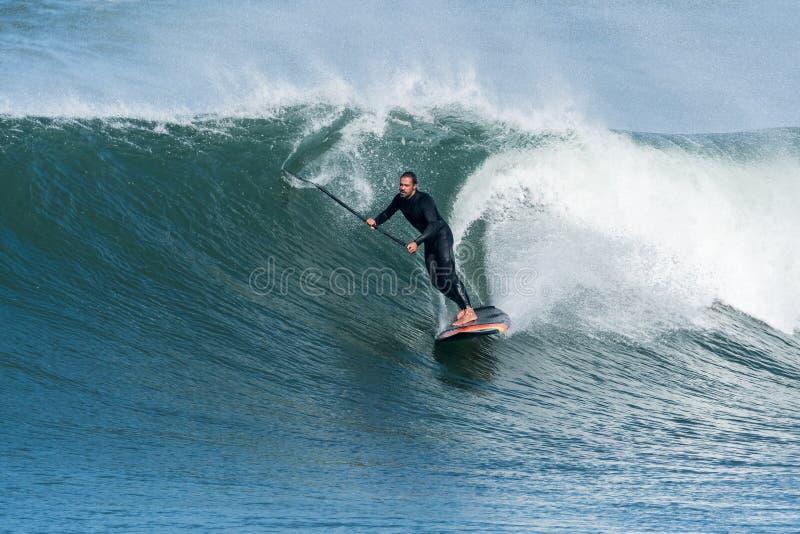 Lev?ntese a la persona que practica surf de la paleta imagen de archivo